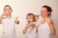 Mom and two blond boys brush their teeth. Family mom and two blond boys brush their teeth royalty free stock image