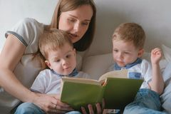 Family mom and two twin brothers toddlers read books laying on the bed. Family reading time. Family mom and two twin brothers toddlers read books laying on the royalty free stock photo