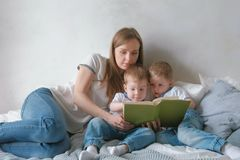 Family mom and two twin brothers toddlers read books laying on the bed. Family reading time. stock photos