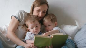 Family mom and two twin brothers toddlers read books laying on the bed. Family reading time. Family mom and two twin brothers toddlers read books laying on the stock footage