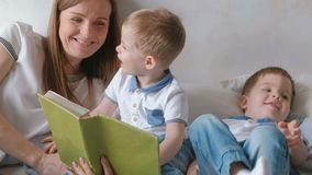 Family mom and two twin brothers toddlers read books laying on the bed. Family reading time. Family mom and two twin brothers toddlers read books laying on the stock video footage