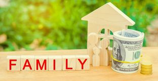 The family with money is standing near their house. concept of wealth life and a happy well-endowed. inscription `family` on woode. N blocks. insurance. savings stock photo