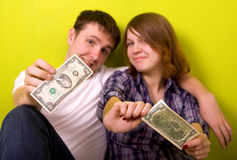 Family moneys. Young family and dollars. On green background. Focus on dollars stock photography