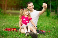 Family is the most important thing. Self portrait of young father and his little daughter smiling while sitting on grass in. Family is the most important thing stock images