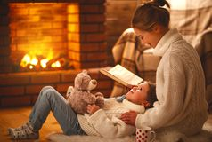 Free Family Mother And Child Reading Book On Winter Evening By Fireplace. Royalty Free Stock Images - 108120349