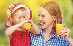 Family mother and baby daughter drinking orange juice in the sum Royalty Free Stock Photos