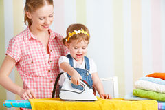 Family mother and baby daughter together engaged in housework ir Royalty Free Stock Photo