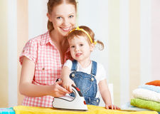 Family mother and baby daughter together engaged in housework ir Stock Image