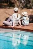 Family safari. Family of mother and child on African safari vacation enjoying wildlife viewing sitting near swimming pool royalty free stock image
