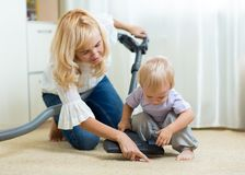 Family mother and child cleaning the room with vacuum-cleaner - housework. Family mother and child boy cleaning the room with vacuum-cleaner - housework Royalty Free Stock Photos