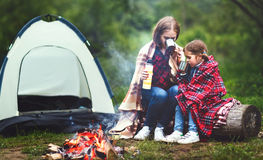 Family mother and child daughter drinking tea on a camping trip. With a tent and by the bonfire royalty free stock image