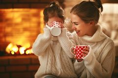 Family mother and child drinking tea and laughing on winter even. Family mother and child daughter drinking tea and laughing on winter evening by fireplace stock photography