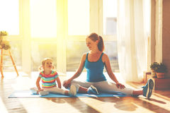 Family mother and child daughter are engaged in fitness, yoga at Stock Photos