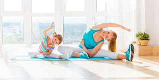 Family mother and child daughter are engaged in fitness, yoga at