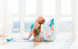 Family mother and child daughter are engaged in fitness, yoga at. Family mother and child daughter are engaged in fitness, yoga, exercise at home Royalty Free Stock Photo
