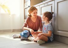 Family mother and child daughter hugging in kitchen on floor stock photos