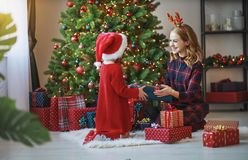 Family mother and child daughter open presents on Christmas mo. Happy family mother and child daughter open presents on Christmas morning stock image