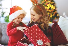 Family mother and child daughter open presents on Christmas mo stock photos