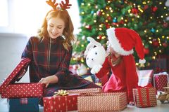 Family mother and child daughter open presents on Christmas mo stock images