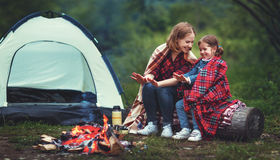Family mother and child daughter warm their hands by bonfire on Royalty Free Stock Images