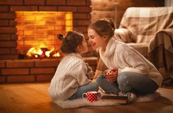 Family mother and child drinking tea and laughing on winter even. Family mother and child daughter drinking tea and laughing on winter evening by fireplace stock images
