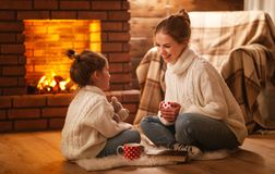 Family mother and child drinking tea and laughing on winter even. Family mother and child daughter drinking tea and laughing on winter evening by fireplace royalty free stock photo