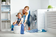 Family mother and child girl  in laundry room near washing machi Royalty Free Stock Image
