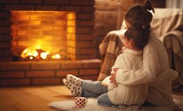 Family mother and child hugs and warm on winter evening by fireplace. Family mother and child daughter hugs and warm on winter evening by fireplace stock images