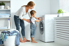 Family mother and child little helper in laundry room near washi. Family mother and child girl little helper in laundry room near washing machine and dirty Royalty Free Stock Photography