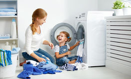 family mother and child little helper in laundry room near washing machine