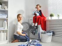 Family mother and child little superhero helper in laundry room Royalty Free Stock Image