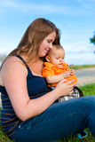 Family - mother and child sitting on a meadow Royalty Free Stock Images