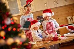 Family of mother and children baking cookies at home Royalty Free Stock Images