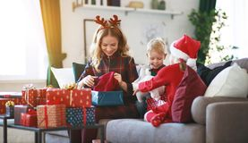 Family mother and children open presents on Christmas morning stock images