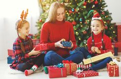 Family mother and children open presents on Christmas morning royalty free stock images
