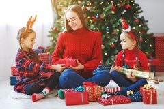 Family mother and children open presents on Christmas morning stock photos
