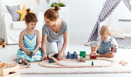 Family mother and children play a toy railway in playroom. Family mother and children play a toy railway in the playroom royalty free stock image