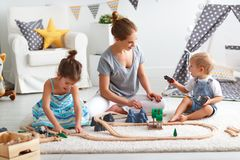Family mother and children play a toy railway in   playroom. Family mother and children play a toy railway in the playroom Stock Images