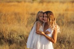 Family. Mother and daughter. Hug. Family, mother and daughter embrace. Girls in white dresses. They are blondes. Family time together royalty free stock photo