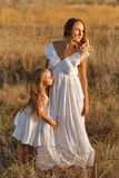 Family. Mother and daughter. Hug. Family, mother and daughter embrace. Girls in white dresses are looking into the distance. They are blondes. Family time royalty free stock images