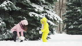 Family of mother and daughter enjoy winter snowy day and playing snowballs stock video