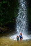Family swimming in waterfall. Family of mother and daughter having fun swimming in waterfall on Saint Lucia island in Caribbean royalty free stock photography