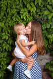 Family, mother and daughter. Mother holds daughter in his arms and kisses her on the cheek Royalty Free Stock Image
