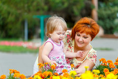 Family, mother and daughter. Family, mother hugging her daughter in the park near a flower bed Stock Images