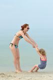Family, mother and daughter playing on the beach. Royalty Free Stock Photography