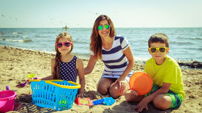 Family mother daughter son having fun on beach. Stock Images