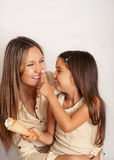 Family of mother and doughter having fun with cream puff, happy Stock Image