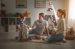 Family mother father and son playing together in children`s pl. Family mother father and baby son playing together in children`s playroom Royalty Free Stock Photo