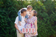 Family of mother father and boy, little boy kissing his mom and parents takes letters LOVE Stock Photo