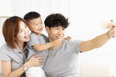 family mother, father and child taking selfie stock images